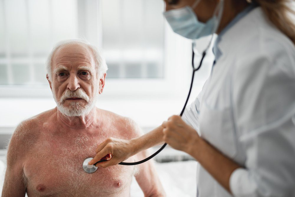 Portrait of shirtless bearded gentleman sitting on hospital bed during medical examination. He is looking away with serious expression