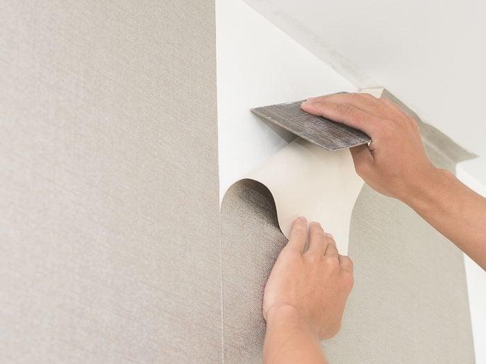 Baking soda uses - Handyman putting up wallpaper on the wall