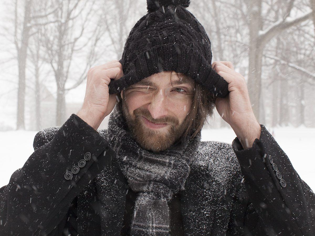 Frostbite symptoms - bundled up man in snowstorm