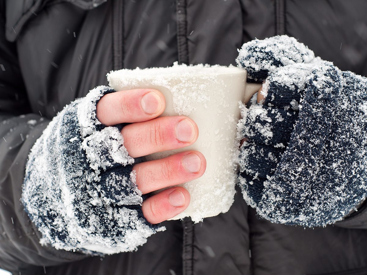 Frostbite symptoms - cold hands holding mug in winter
