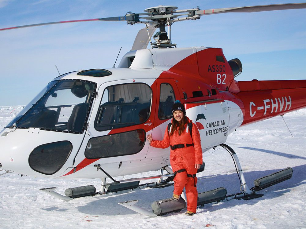 Kate posing next to helicopter