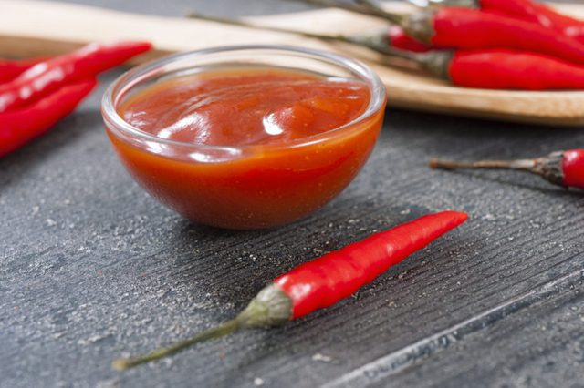 chili fruits and red pepper powder on old black wood table