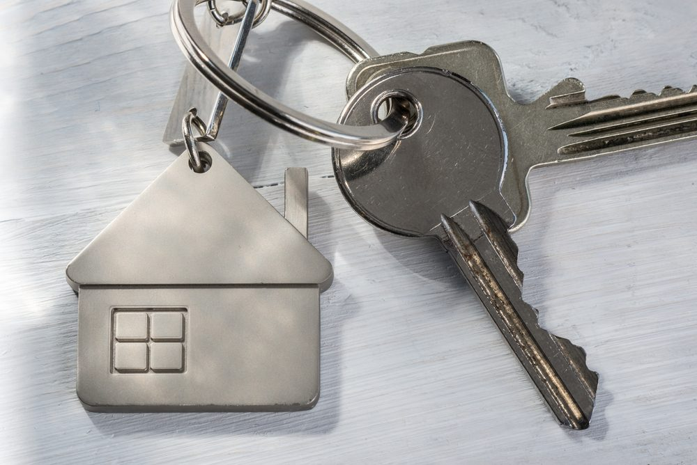 Real estate concept - Keys on white wooden sunny background
