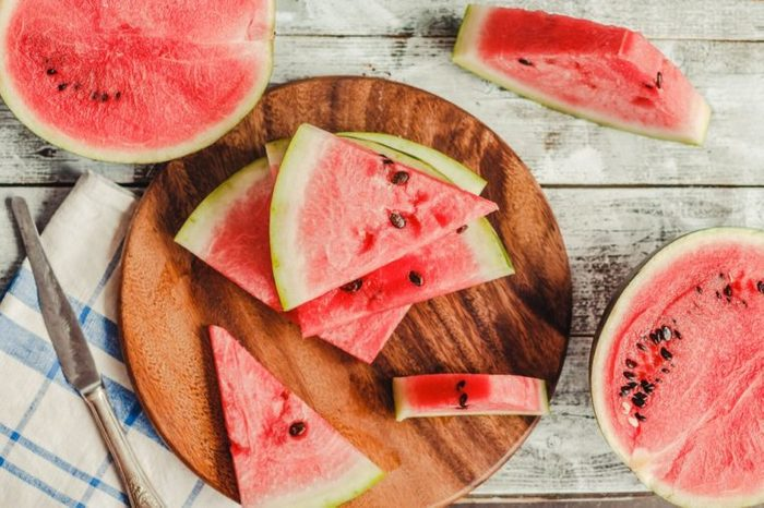 Watermelon slice on a blue rustic wood background.Summer fruit, raw food concept. Top view.