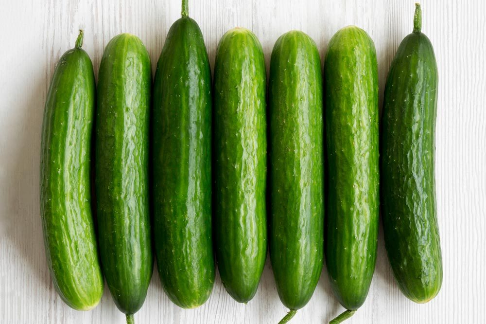 Flat lay of raw organic green cucumbers on white wooden surface. Top view, from above, overhead. Close-up.