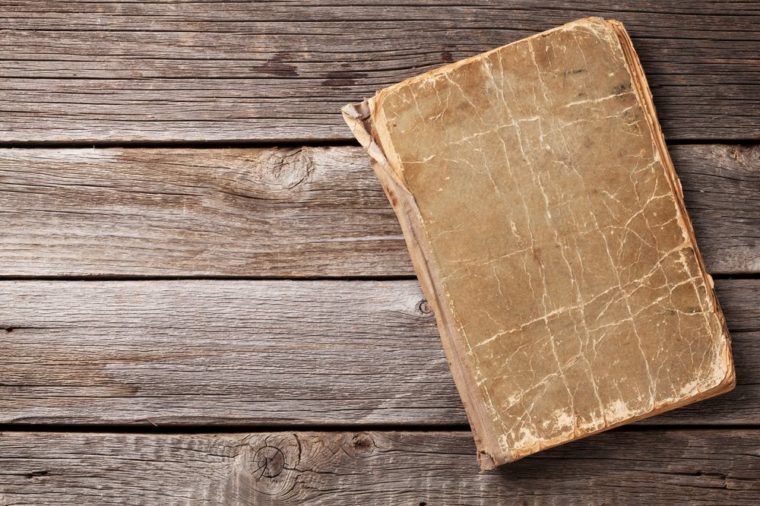 Vintage book on wooden background. Top view with copy space