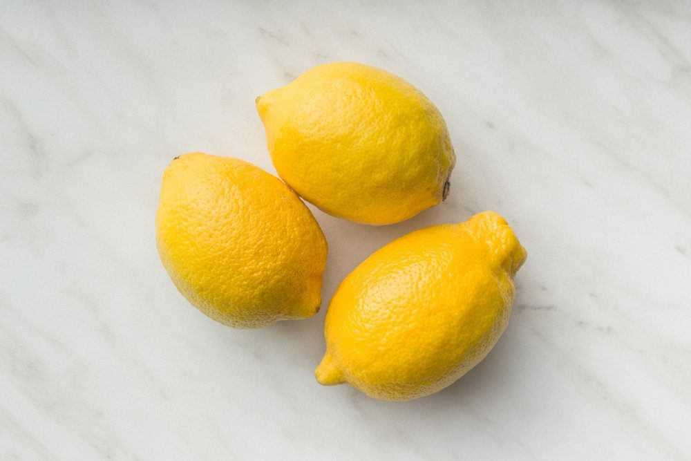 Three yellow lemons on table. Top view.