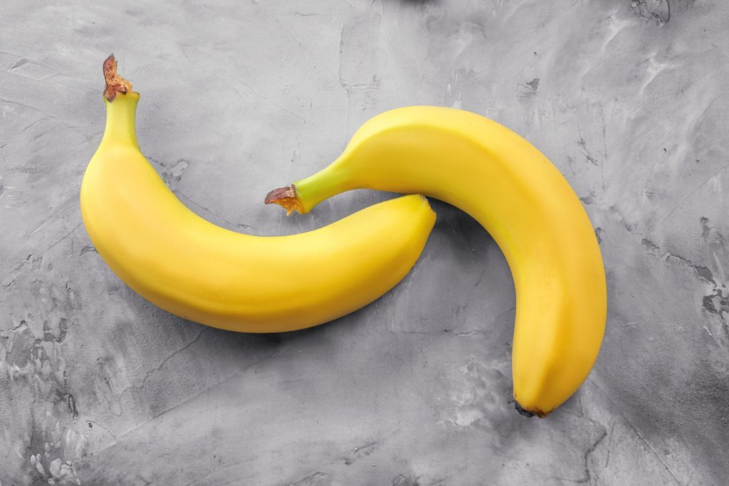Ripe bananas on grey textured background