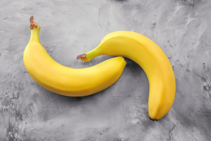 Ripe bananas on grey textured background