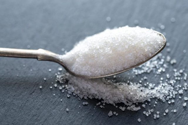 Spoon with white sugar on the dark background