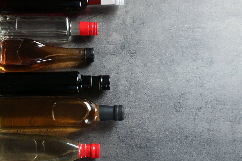 Bottles with different kinds of vinegar and space for text on grey background, flat lay