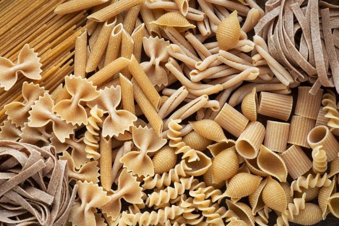Variety of types and shapes of dry wholemeal pasta