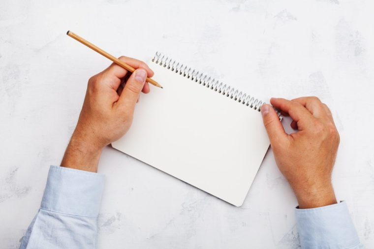 Lefty writes in clean notebook on white table top view. Left handed concept.