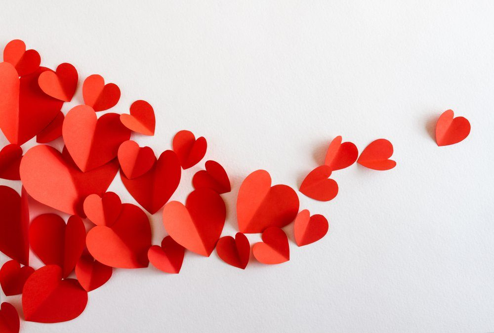 Flying red paper hearts on white background. Valentine's Day. Symbol of love. Copy space.