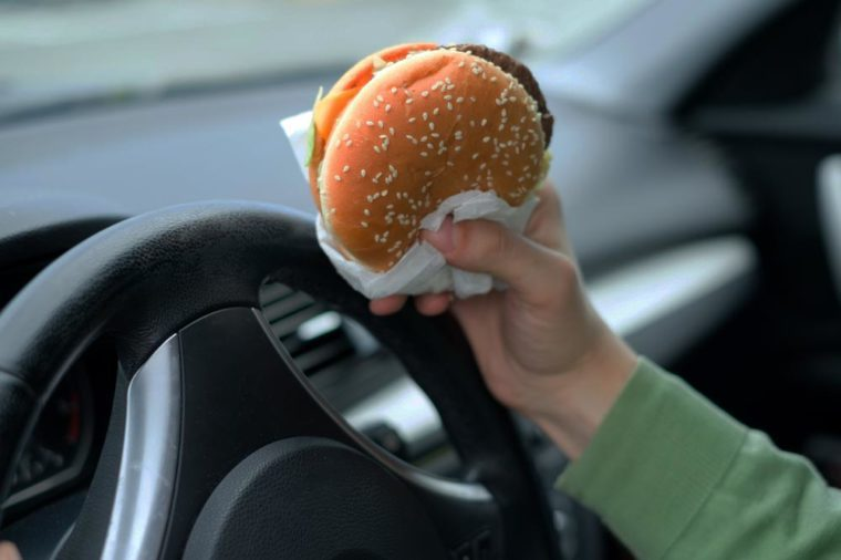 Close up of driver's hand at the wheel while eating food in the traffic