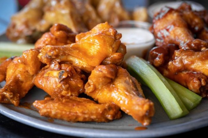 Close up on a platter of spicy buffalo chicken wings with space for text on the right