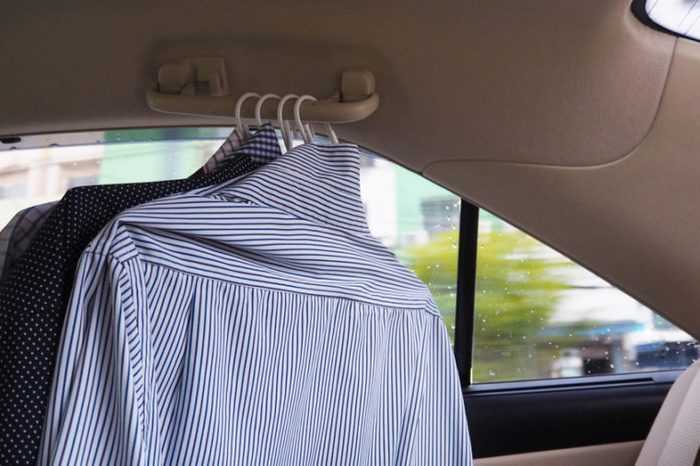 Many shirts hang in the car.