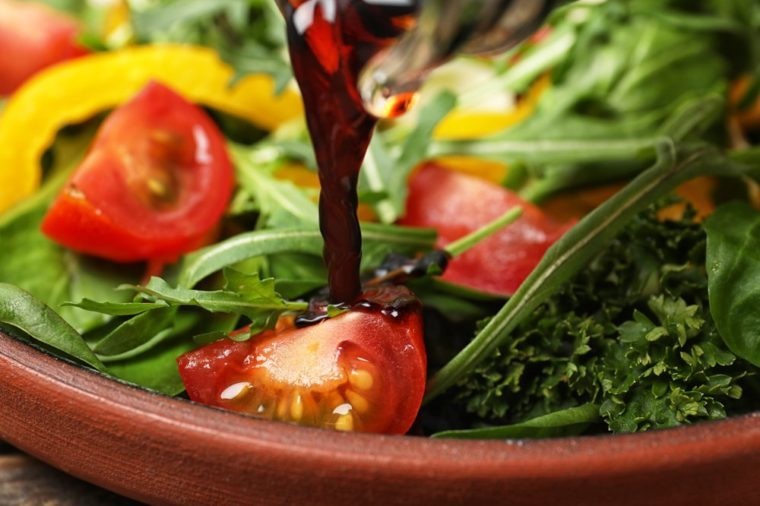 Pouring balsamic vinegar to fresh vegetable salad on plate, closeup
