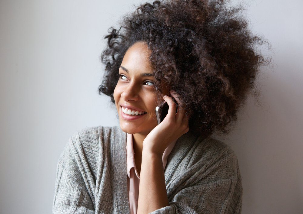 Close up portrait of a cheerful young woman talking on mobile phone