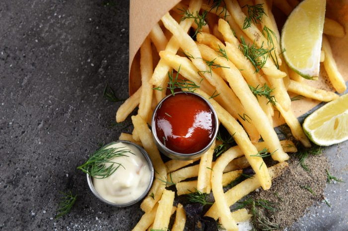 French fries in bag with sauce, lime and spice on table