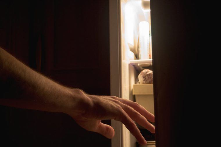 a hand reaches for the fridge at night