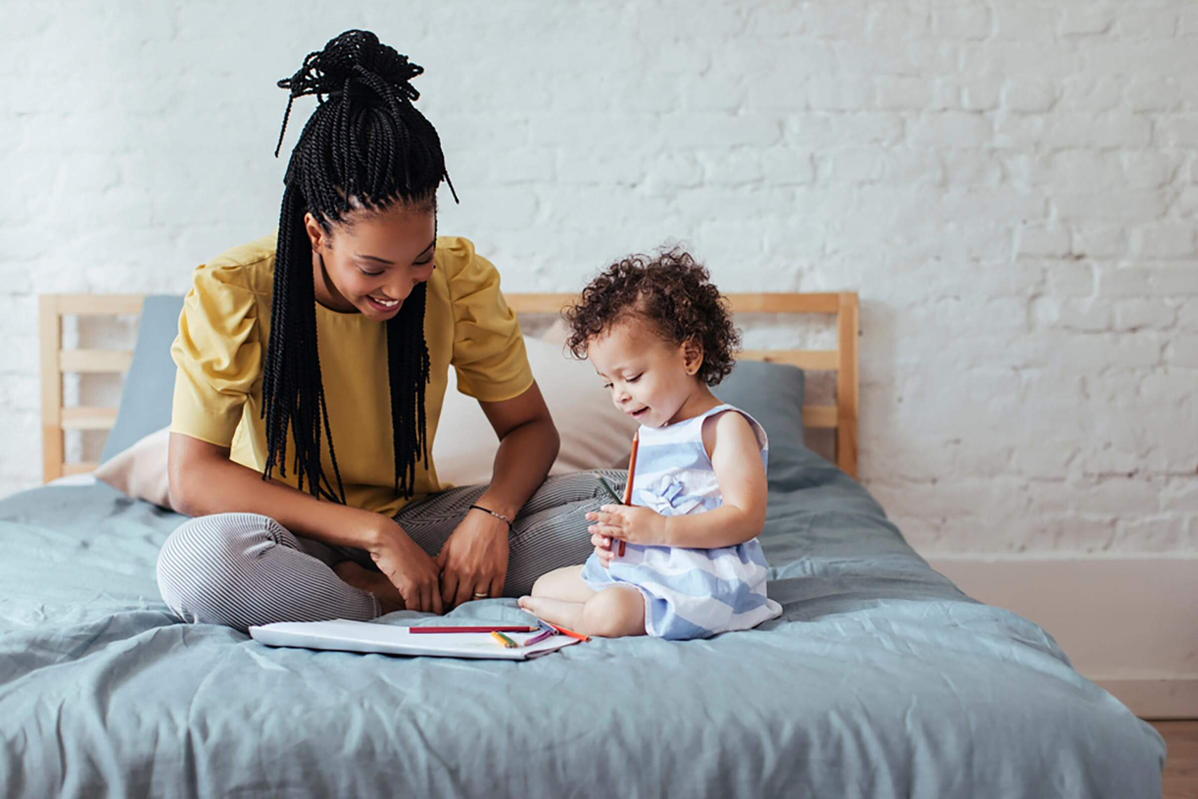 Beautiful African woman sitting on bed with her baby daughter and drawing on paper.