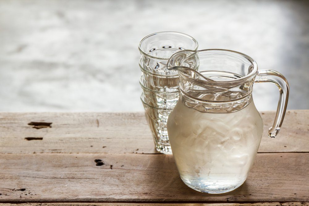 Glass pitcher of water and glass on wooden table background.