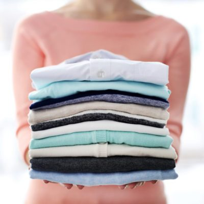 Woman holding folded pile of clothes