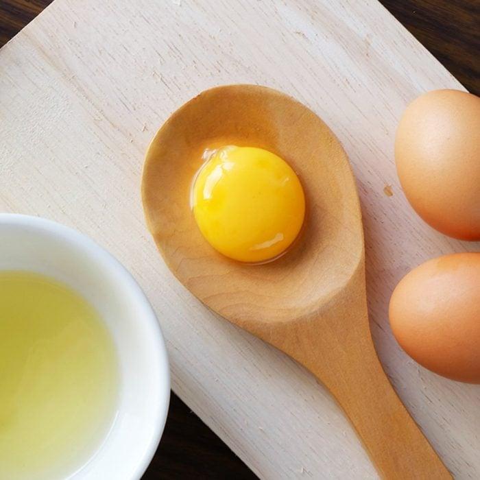 Egg yolk on wooden spoon