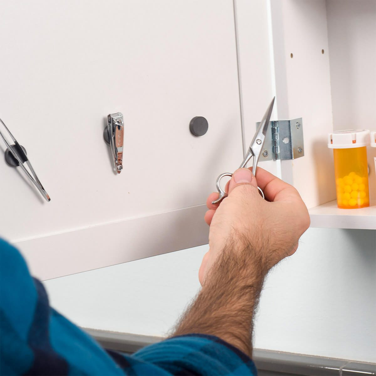 Home organizing hacks mount magnets inside a medicine cabinet