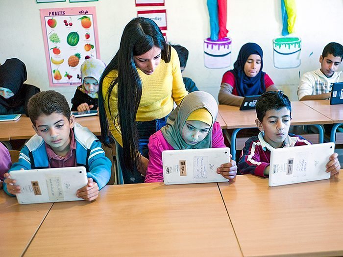"""Riman Ezzeddine looks over Takwa's shoulder as the class of older children—eight- to-15-year-olds—work on their tablets during a lesson in the """"Hive""""."""