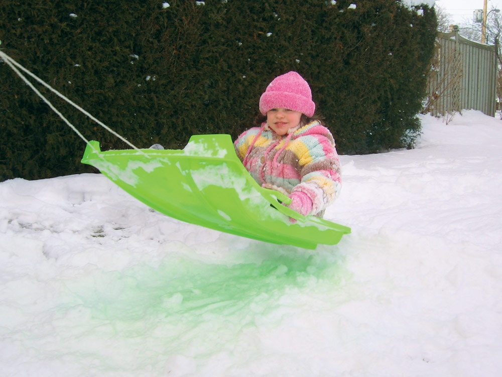 Little girl snow sledding
