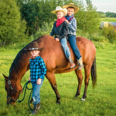 Cute kids dressed as cowboys with a horse