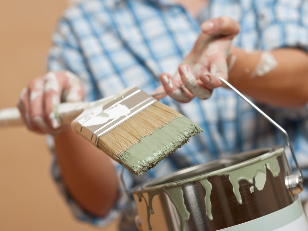 Woman holding paint brush and paint can
