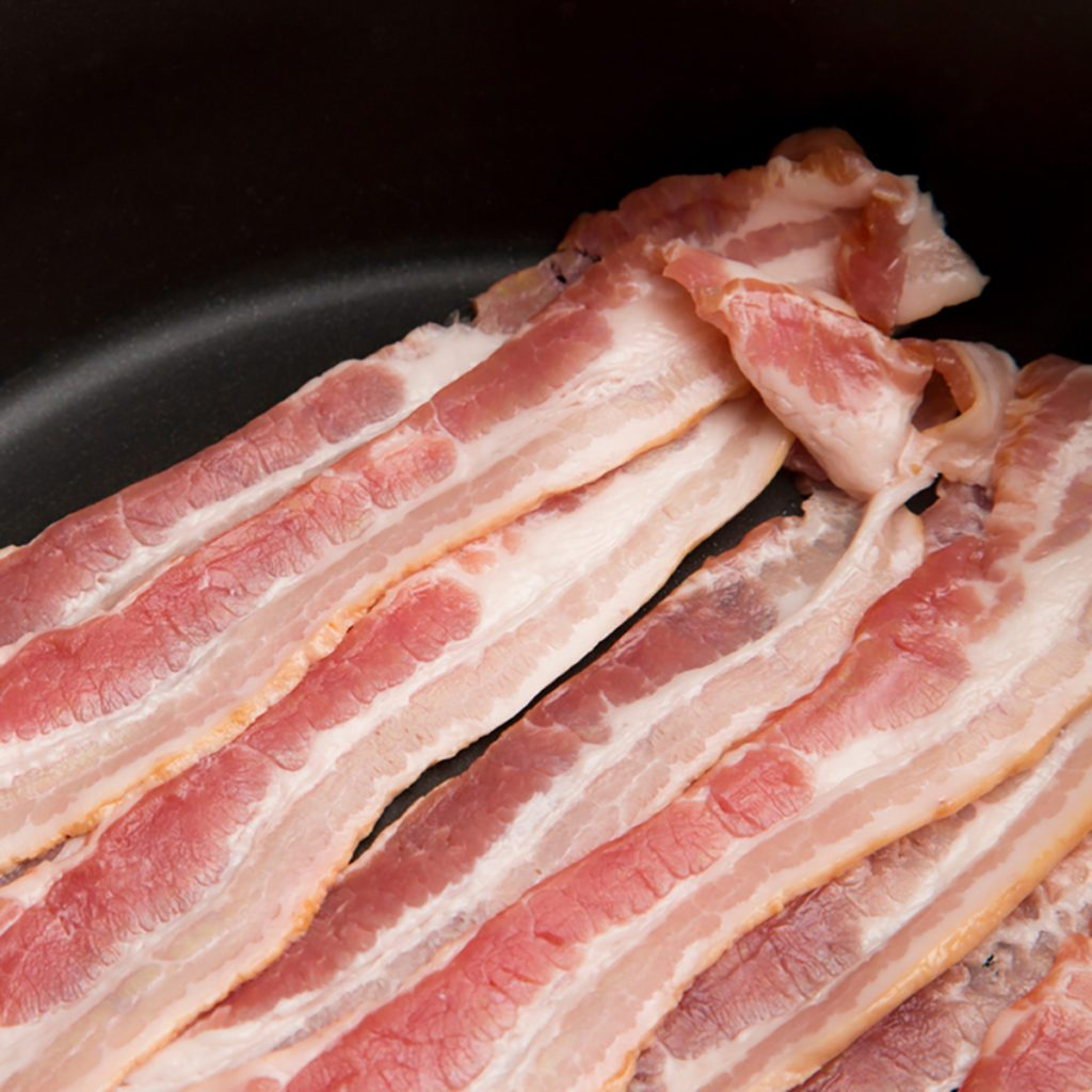 Raw American Style Bacon in a Frying Pan