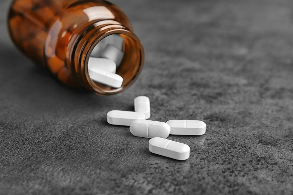 Bottle with pills on grey background