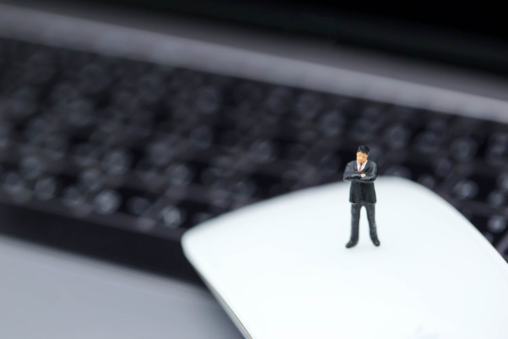 Miniature people : Businessman standing on mouse of laptop.
