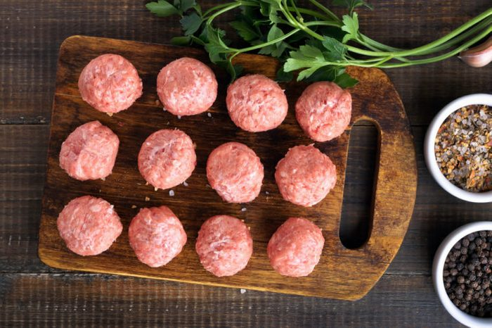 Raw meatballs on a cutting board, top view