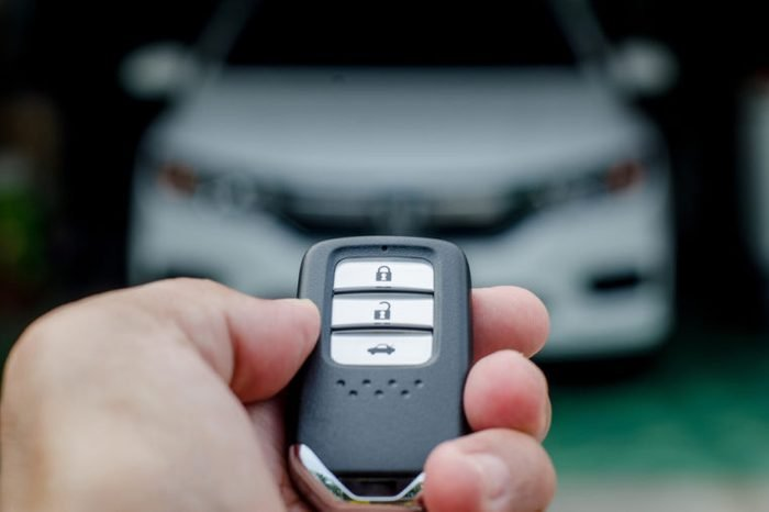 Car smart key is an electronic access and authorization system, Hand holding smart key of car.