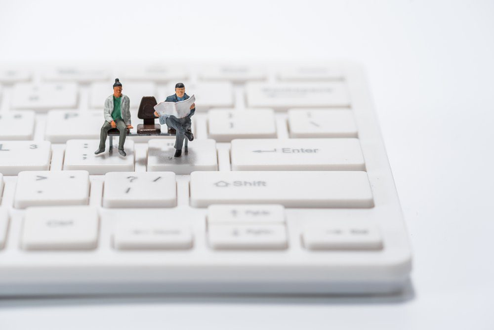 miniature people figure sitting on bench on computer keyboard background