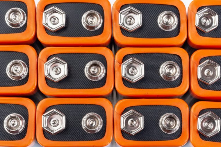 Background image of a large number of orange batteries, standing in several rows.