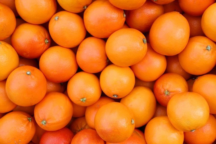 background of juicy ripe oranges freshly picked from the orchard tree