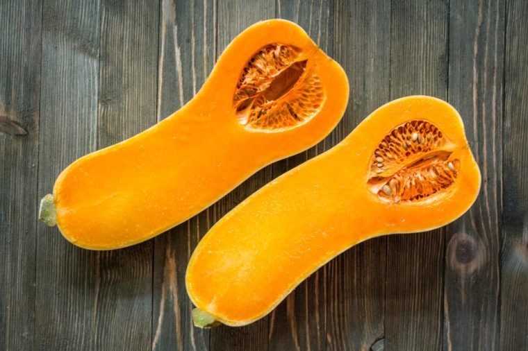 Two halves of butternut squash on a wooden surface.