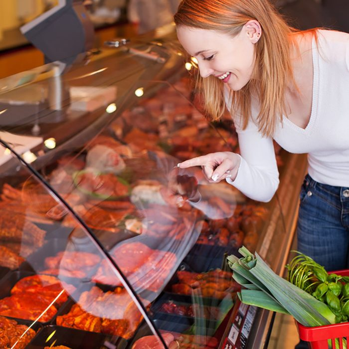 Happy young woman choosing meat from glass cabinet in grocery store