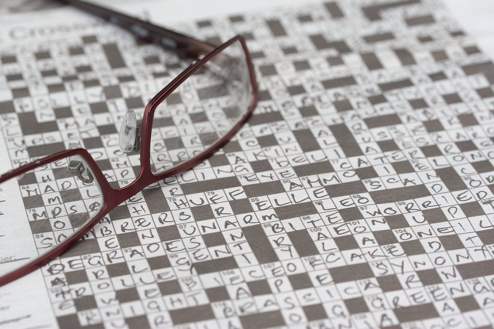 A completed crossword puzzle with a pair of reading glasses.