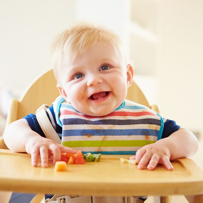 Baby Boy Eating Fruit In High Chair; Shutterstock ID 177222725