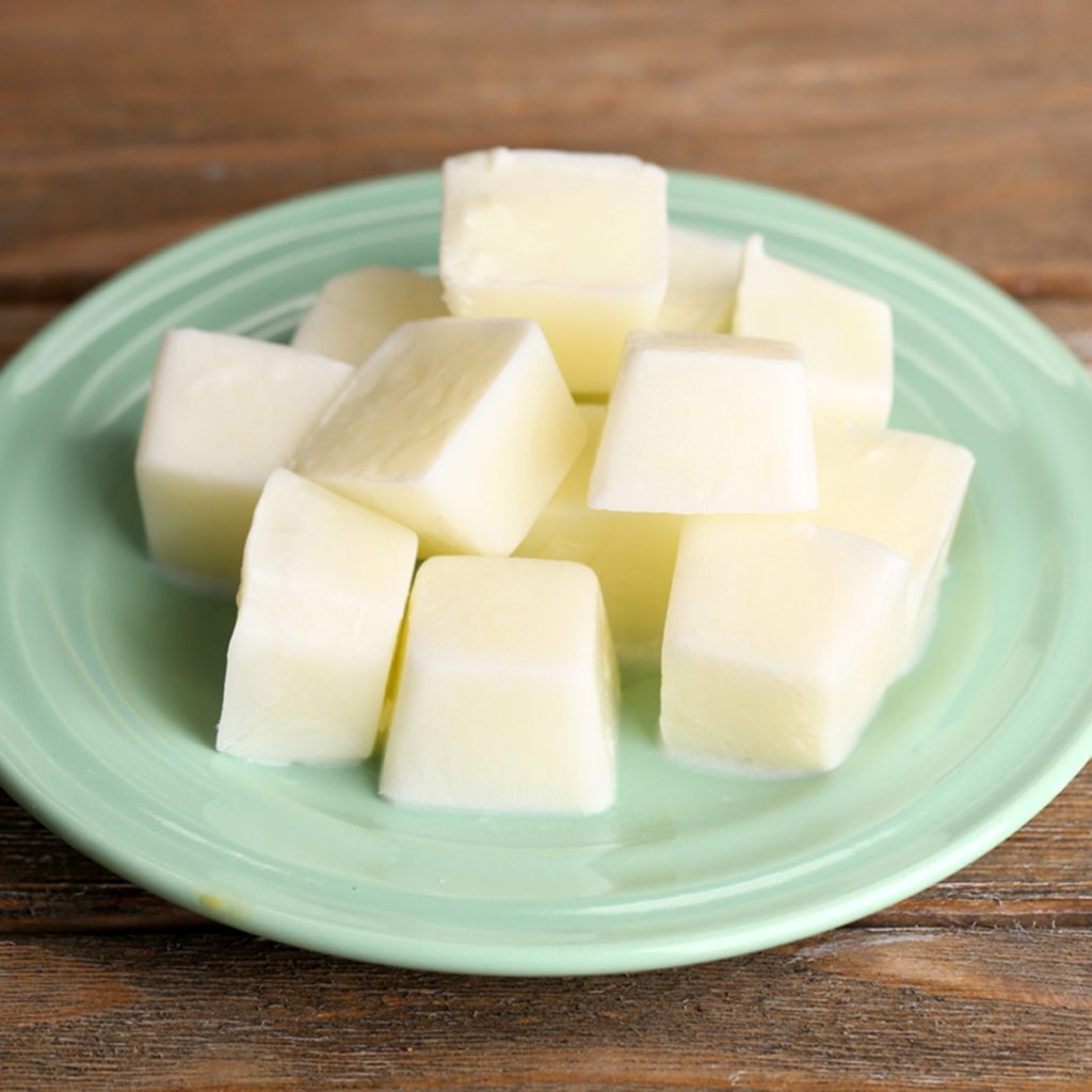 Milk ice cubes on plate on wooden background; Shutterstock ID 221290927