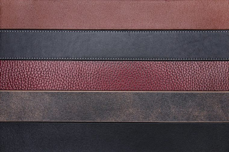 Dark natural leather belts close-up texture background