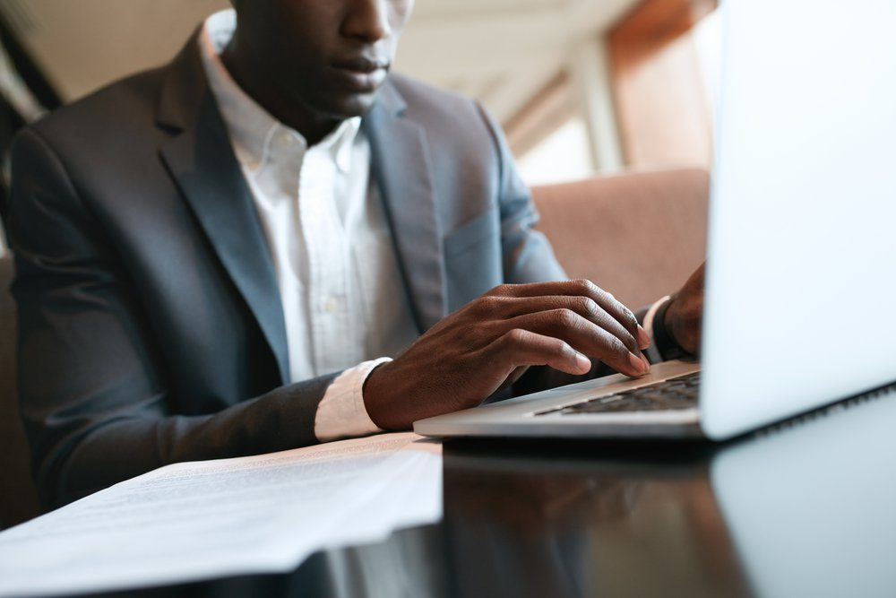 Close up shot of male hands typing on laptop keyboard. African businessman working on laptop computer at cafe.