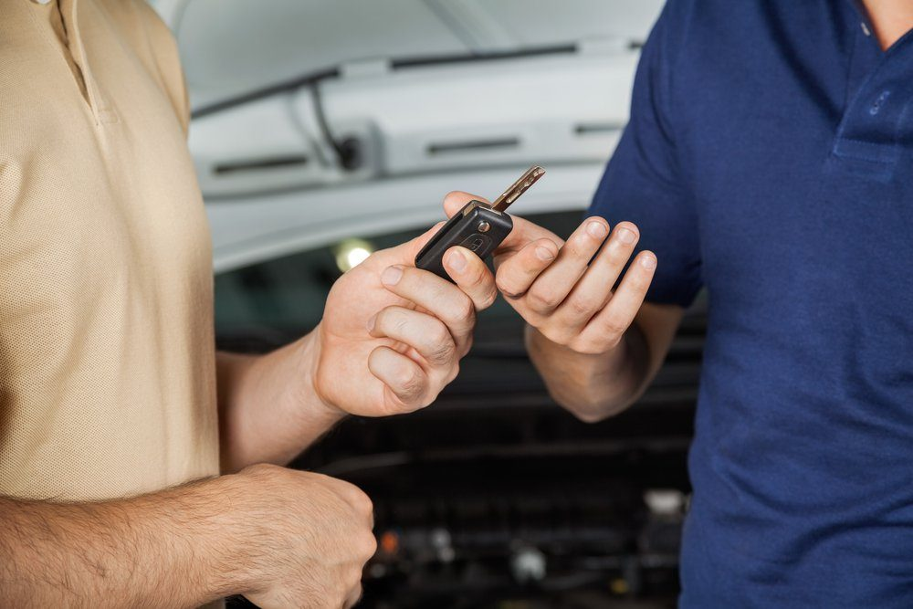 Midsection of male client giving car key to mechanic in auto repair shop